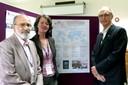 Guilherme Ary Plonski, Britta Padberg e Martin Grossmann ao lado do cartaz que apresenta o IEA-USP